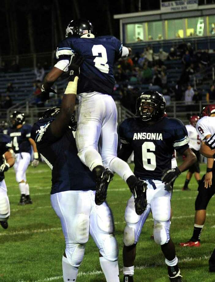 Ansonia's #2 Arkeel Newsome is lifted into the air by a teammate after he brought in a touchdown during boys football action against Torrington in Ansonia, Conn. on Thursday September 14, 2011. Photo: Christian Abraham / Connecticut Post