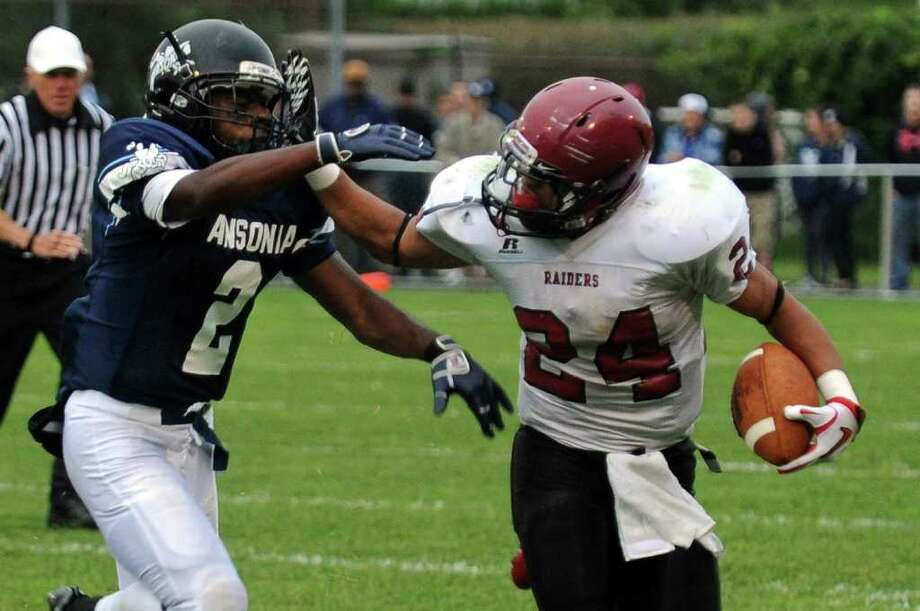 Highlights from boys football action between Ansonia and Torrington in Ansonia, Conn. on Thursday September 14, 2011. Torringotn's #24 Brenden Lytton, right, fends of Ansonia's Arkeel Newsome. Photo: Christian Abraham / Connecticut Post