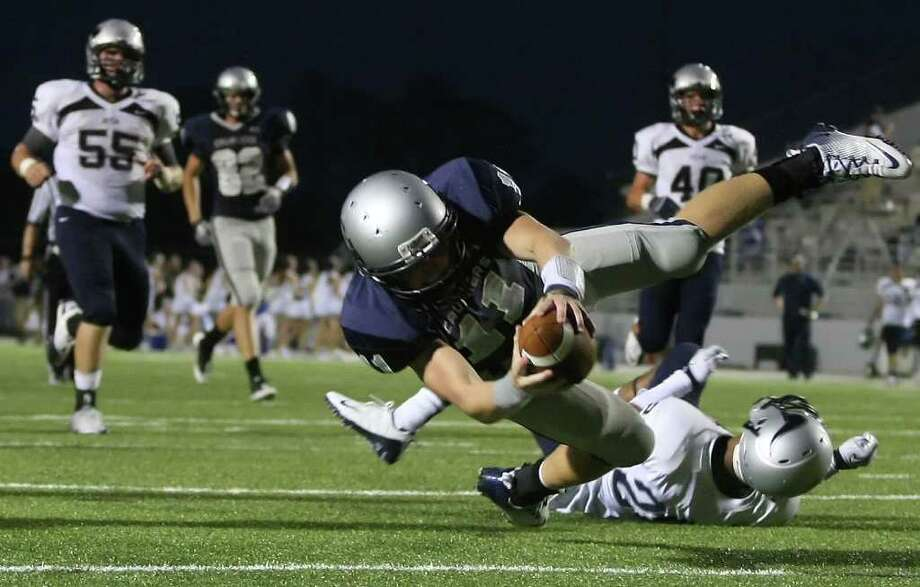 ERIC CHRISTIAN SMITH: FOR THE CHRONICLE SCORE THE DIVE A SIX: College Park's Zach Wright lunges into the end zone past Bryan's Johnny Childs to cap a 37-yard touchdown run in first-half action Thursday night. Photo: Eric Christian Smith