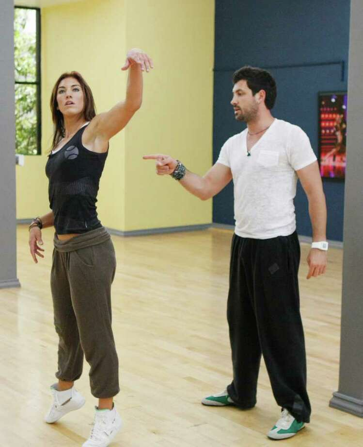 "In this Sept. 2, 2011, image released by ABC, professional soccer player Hope Solo, left, is shown with her dance partner Maksim Chmerkovskiy during a rehearsal for the celebrity dance competition series ""Dancing with the Stars,"" in Los Angeles. (AP Photo/ABC, Rick Rowell) Photo: Rick Rowell"