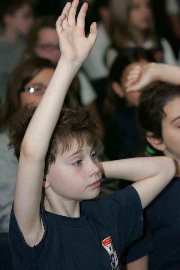 Greenwich Catholic School fourth grader Frank Riccio raises his hand to ask a question of Sharon Robinson, daughter of baseball legend Jackie Robinson, during her visit to the school Friday morning. Photo: David Ames / Greenwich Time