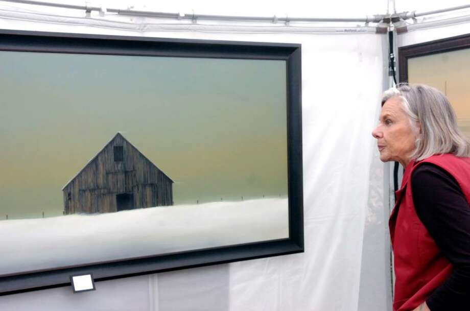 "Kaysie Goodenough eyes painter Gary Stretar's ""Winter Barn"" as she browses the Bruce Museum's 28th annual Outdoor Arts Festival Saturday morning, Oct. 10, 2009. The festival is a juried event featuring more than 90 artists selected from across the country and features paintings, photography, drawings, prints, sculptures and mixed media pieces. It continues through Sunday running from 10 a.m. to 5 p.m. on the museum's grounds, Photo: Keelin Daly / Greenwich Time"