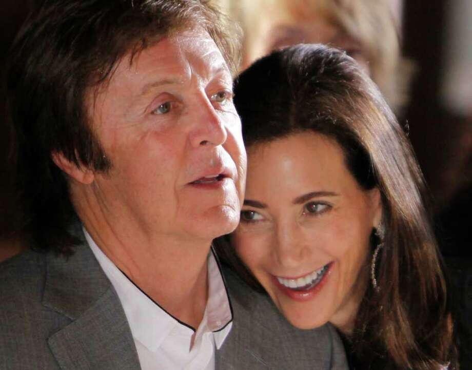 FILE -  This is a Monday, Oct. 4, 2010 file photo of British musician Paul McCartney and his girlfriend Nancy Shevell as they watch Stella McCartney's spring-summer 2011 ready to wear fashion collection show in Paris. Paul McCartney is set to tie the knot at the venue where he first married more than 40 years ago. Officials said Friday Sept. 16, 2011 that the former Beatle and fiancee Nancy Shevell have posted a notice of intention to marry at London's Marylebone Register Office. (AP Photo/Thibault Camus) Photo: Thibault Camus / AP