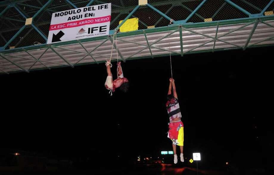 Los cuerpos de un hombre (der.) y una mujer presuntamente asesinados por el grupo de narcos de los Zetas fueron colgados, con mensajes y amenazas sobre el uso de las redes sociales, de un puente peatonal de Nuevo Laredo, México, el 13 de septiemere de 2011. Photo: RAUL LLAMAS / AFP