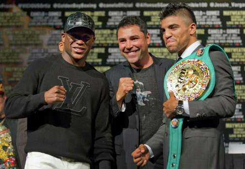 Floyd Mayweather, left, and Victor Ortiz, right, pose for a photo with Oscar De La Hoya after a news conference previewing their upcoming fight, Wednesday, Sept. 14, 2011, in Las Vegas. Mayweather is scheduled to challenge Ortiz for his WBC welterweight title Saturday. Photo: AP
