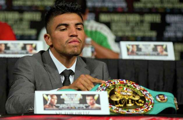 Victor Ortiz displays his WBC welterweight title belt on the table during a boxing news conference, Wednesday, Sept. 14, 2011, in Las Vegas. Ortiz is slated to defend hist title against Floyd Mayweather on Saturday, Sept. 17. Photo: AP