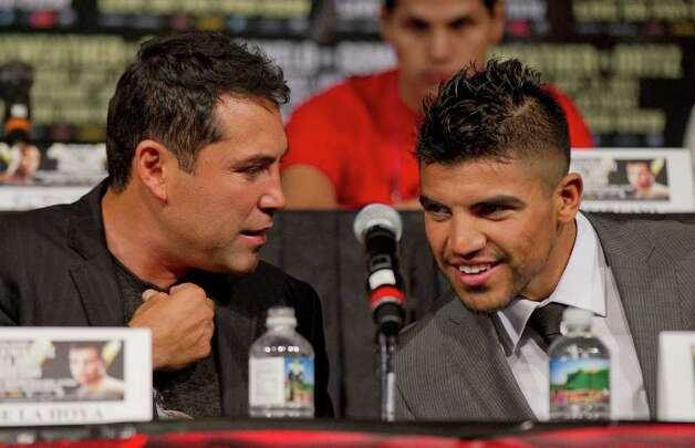 Oscar De La Hoya, left, talks with Victor Ortiz during a boxing press conference, Wednesday, Sept. 14, 2011, in Las Vegas. Ortiz is slated to defend his WBC welterweight title against Floyd Mayweather on Saturday, Sept. 17. Photo: AP