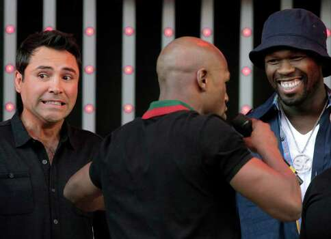 Boxing promoter and former champion Oscar De La Hoya, left, and rapper 50 Cent, right, react as they listen to Floyd Mayweather at CityWalk in Universal City, Calif., Monday, Sept. 12, 2011. Mayweather is scheduled to fight champion Victor Ortiz in a WBC welterweight title match Saturday in Las Vegas. Photo: AP