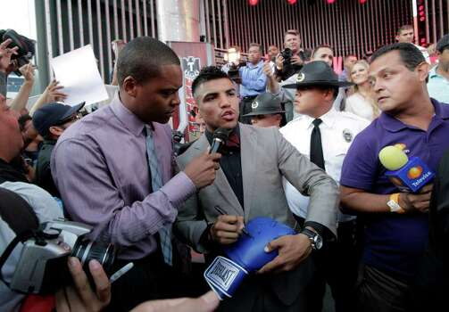 Boxer Victor Ortiz, center, talks to reporters as he signs autographs for fans at CityWalk in Universal City, Calif., Monday, Sept. 12, 2011. Ortiz is scheduled to fight Floyd Mayweather in a WBC welterweight title match Saturday in Las Vegas. Photo: AP