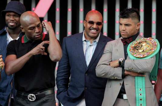 Boxer Floyd Mayweather Jr., left, looks at his biceps as he poses with Victor Ortiz, right, at CityWalk in Universal City, Calif., Monday, Sept. 12, 2011. The two will fight in a WBC welterweight title match, Saturday in Las Vegas. Photo: AP