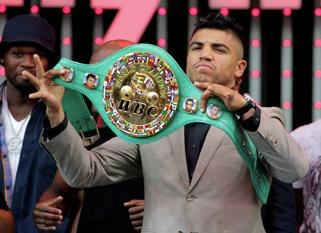 Boxer Victor Ortiz holds up a championship belt as he poses for photos at CityWalk in Universal City, Calif., Monday, Sept. 12, 2011. Ortiz is scheduled to fight Floyd Mayweather in a WBC welterweight title match Saturday in Las Vegas. Photo: AP