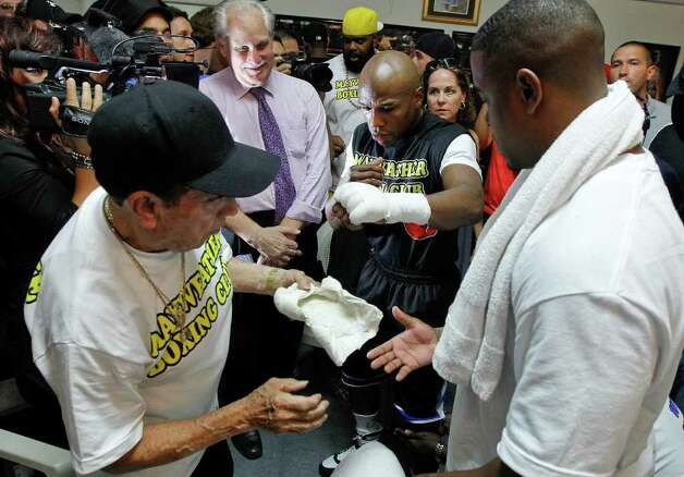 Floyd Mayweather, center, has his hands wrapped by Rafael Garcia, left, before working out at his gym, Tuesday, Sept. 6, 2011, in Las Vegas. Mayweather will fight Victor Ortiz on Sept. 17 for the WBC World Welterweight championship. Photo: AP