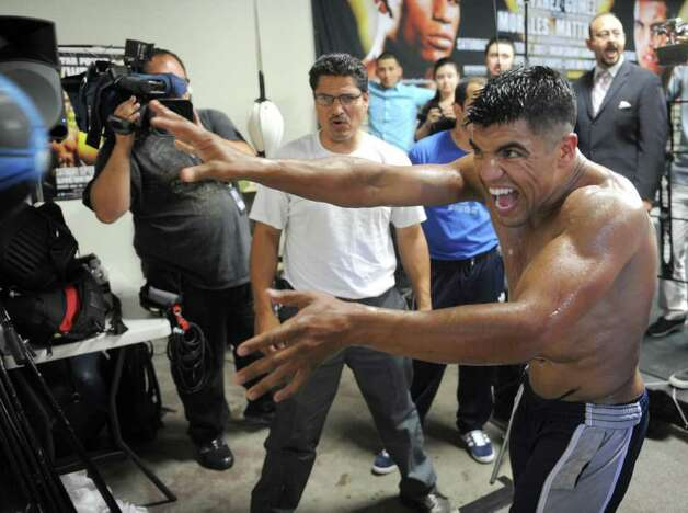 Victor Ortiz throws a medicine ball at the wall next to his trainer, Danny Ortiz, while getting ready for a Sept. 17 boxing match against Floyd Mayweather Jr., Tuesday, Aug. 30, 2011, in Ventura, Calif. (AP Photo/Ventura County Star, Juan Carlo) LOS ANGELES TIMES OUT  LOS ANGELES DAILY NEWS OUT  MAGS OUT Photo: AP