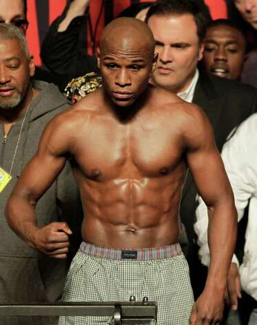 Floyd Mayweather Jr., center, poses on the scale during the weigh-in for his WBA welterweight boxing title fight against Shane Mosley Friday, April 30, 2010, in Las Vegas. Mayweather weighed in at 146-pounds. ( Photo: AP