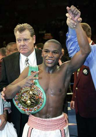Floyd Mayweather Jr. of the U.S. poses with the WBC belt after defeating WBC welterweight champion Carlos Baldomir of Argentina by unanimous decision at the Mandalay Bay Events Center in Las Vegas, Nevada November 4, 2006. Promoter Dan Goosen is at left. REUTERS/Steve Marcus (UNITED STATES) Photo: STEVE MARCUS, REUTERS / X00642