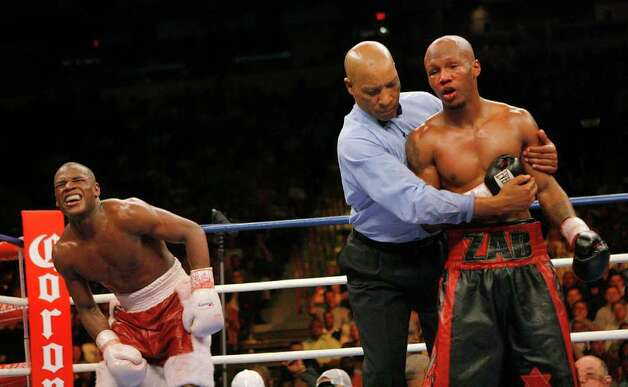 Floyd Mayweather Jr., left, reacts after he was punched below the belt by Zab Judah, right, in the 10th round of their IBF welterweight title boxing match at Thomas and Mack Center in Las Vegas, Saturday, April 8, 2006.  Mayweather won by unanimous decision after the 12th round. Photo: JAE C. HONG, AP / AP