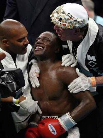 Floyd Mayweather Jr., of Las Vegas, Nev., kneels on the canvas as he reacts as he was declared the winner after six rounds against  Arturo Gatti of Jersey City, N. J. in their WBO World Super Lightweight Championship bout at Atlantic City's Boardwalk Hall Saturday, June 25, 2005 in Atlantic City, N.J.. It looked like Gatti's corner stopped the fight. With Mayweather are cut man Rafael Garcia, right, and Advisor Leonard Ellebar. Photo: Mel Evans, AP / AP