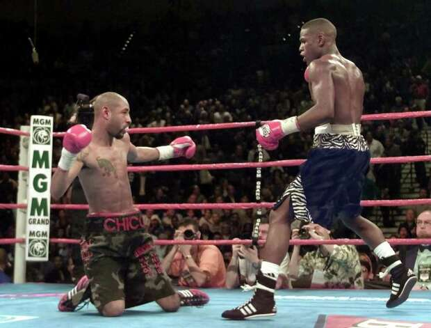 Floyd Mayweather, right, of Grand Rapids, Mich., sends Diego Corrales, left, of Sacramento, Calif., to the mat during the 10th    round to end their WBC super featherweight championship fight in Las Vegas, Saturday, Jan. 20, 2001. Mayweather retained his title. Photo: ERIC RISBERG, AP / AP