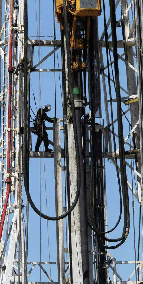 JOHN DAVENPORT : San Antonio Express-News EAGLE FORD PERCH: A worker goes about his day high up on a rig between Fowlerton and Cotulla. A new report sees a bounty of U.S. natural gas and oil. Photo: JOHN DAVENPORT / SAN ANTONIO EXPRESS-NEWS (Photo may be sold to the public)