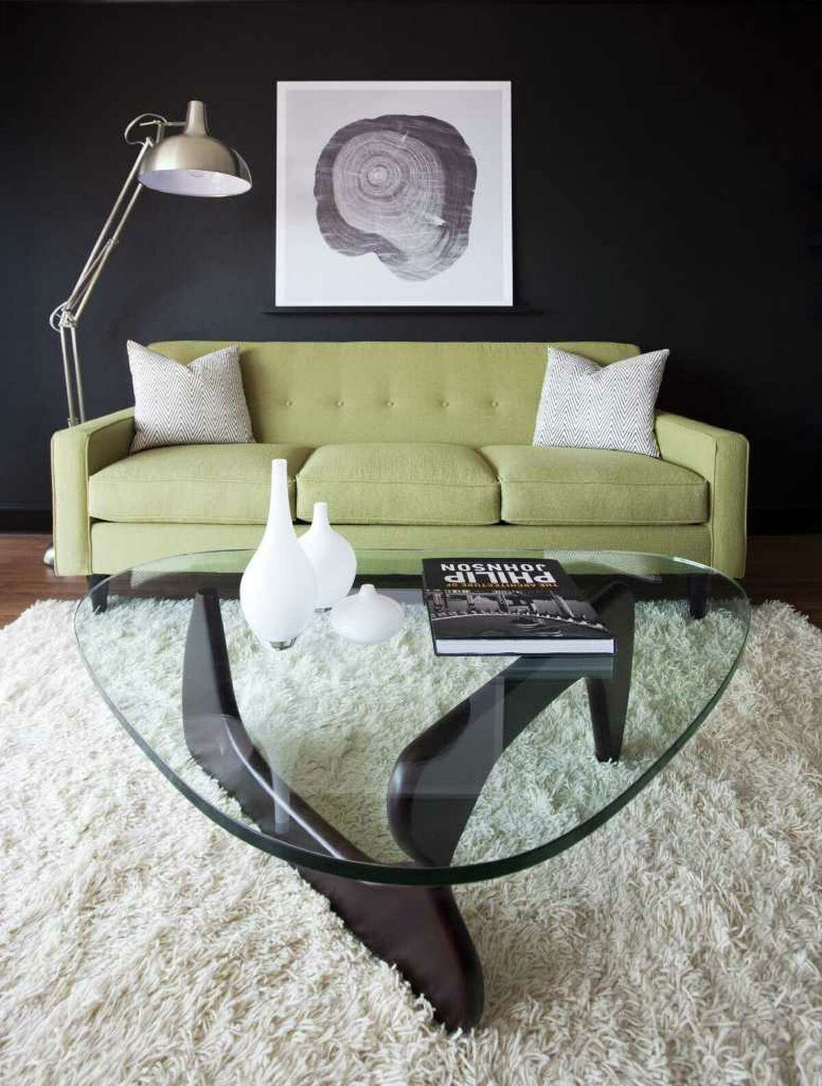 CREATING CONTRAST: For his model unit at Houston House, designer Chris Nguyen painted one of the walls black and placed a clean-lined, modern chartreuse sofa in front of the wall in the living room. The contrast is further accentuated by a high-pile, white shag rug and black and white patterned pillows.