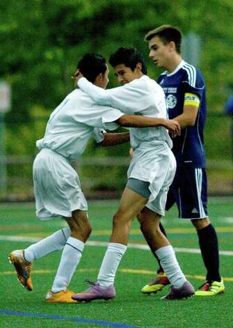 Abbott Tech's Santiago Sanchez, left, congratulates David Farinango on his goal as Wolcott Tech's Troy Gustafson, right, walks by in the second half of their game at Broadview Middle School in Danbury on Thursday, Sept. 15, 2011. Abbott Tech won 4-0. Photo: Jason Rearick / The News-Times