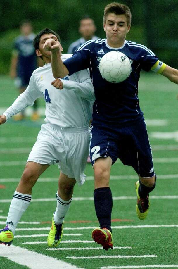Abbott Tech's Carlos Sanchez, left, fights Wolcott Tech's Troy Gustafson over control of the ball during their game at Broadview Middle School in Danbury on Thursday, Sept. 15, 2011. Abbott Tech won 4-0. Photo: Jason Rearick / The News-Times