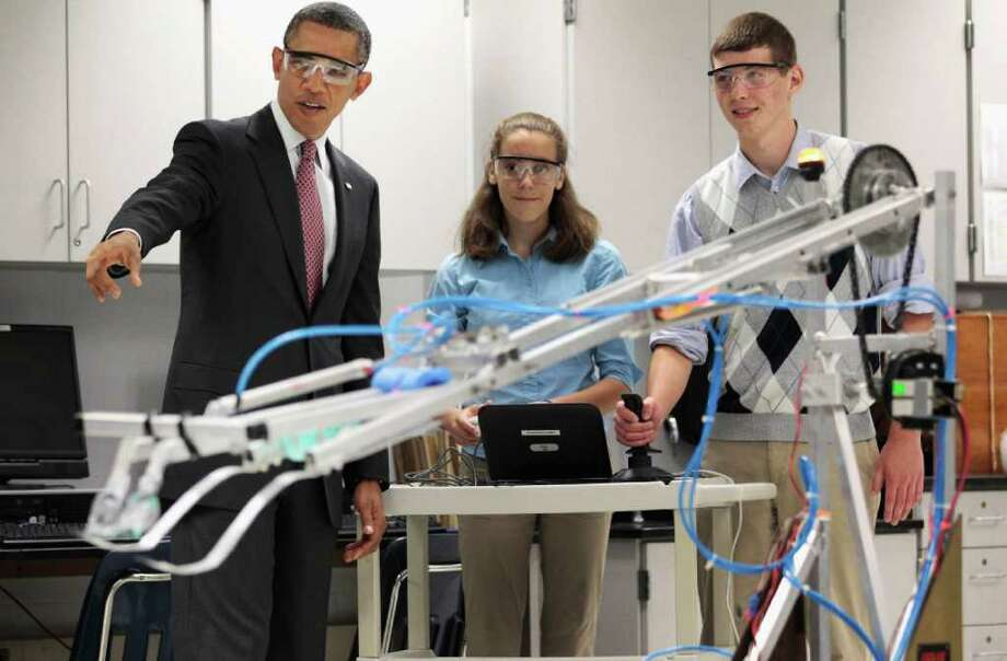 CHIP SOMODEVILLA : GETTY IMAGES  AMERICAN INGENUITY: President Barack Obama watches students Meghan Clark and Nathan Hughes demonstrate a robot created in Thomas Jefferson High School's labs in Alexandria, Va. He later signed a bill that is the first major reform of patent law since 1952. Photo: Chip Somodevilla / 2011 Getty Images