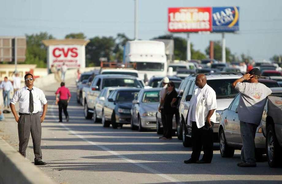 William Yokie, izq., observa el tráfico junto a otros conductores atascados en la autopista I-45 al norte de Houston, cerca de Airline Road, después de un accidente provocado por un camión de carga el martes 9 de agosto de 2011. Photo: Karen Warren / © 2011 Houston Chronicle