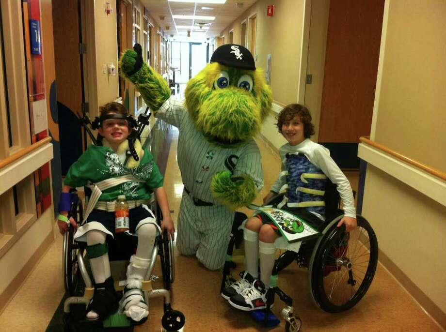 Aaron Berry, 8, and his 9-year-old brother, Peter encounter the Chicago White Sox's wacky mascot, Southpaw, during their recent hospital stay in Chicago. (Family photo) Photo: Family Photo