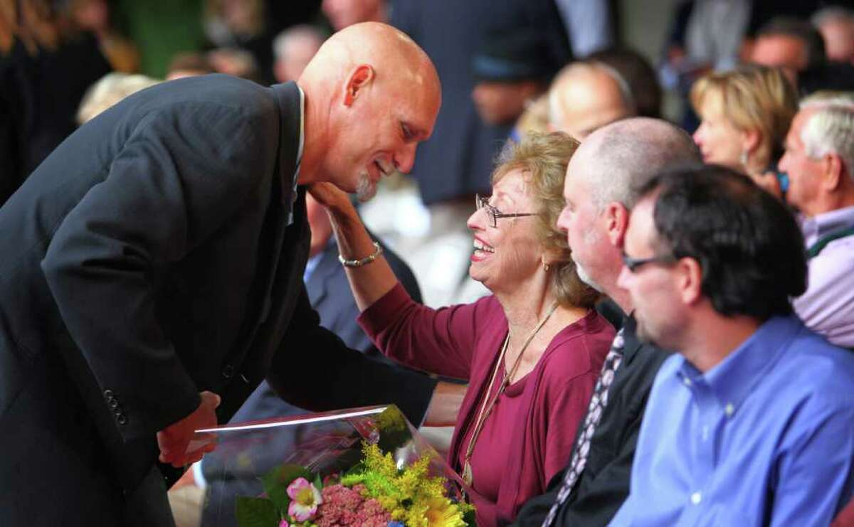 Former Mariner Jay Buhner greets Marilyn Niehaus during the unveiling of a statue memorializing her late husband, the voice of the Mariners, Dave Niehaus. Niehaus, who died in 2010, was the broadcast voice of the team for decades.
