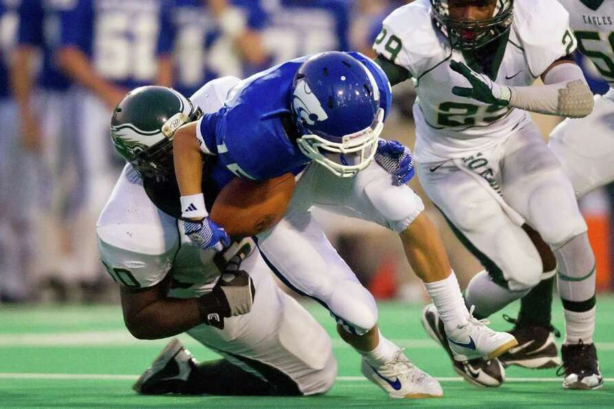 Cy Creek receiver Kyle Huff, center, fumbles as he is hit by Cy Falls defensive lineman Kevon Hunter