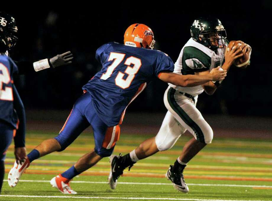 Norwalk quarterback Delshawn Wilson, right, evades a Danbury defender at Danbury High School on Friday, Sept. 16, 2011. Photo: Jason Rearick / The News-Times