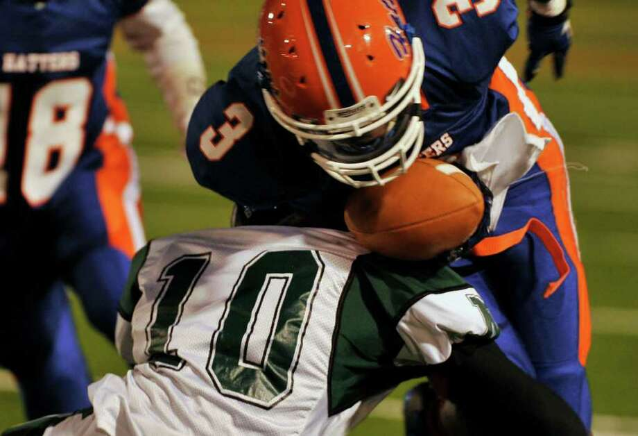 Norwalk's Andy St. Fleur, bottom, puts the hit on Danbury's James Harrington at Danbury High School on Friday, Sept. 16, 2011. Photo: Jason Rearick / The News-Times