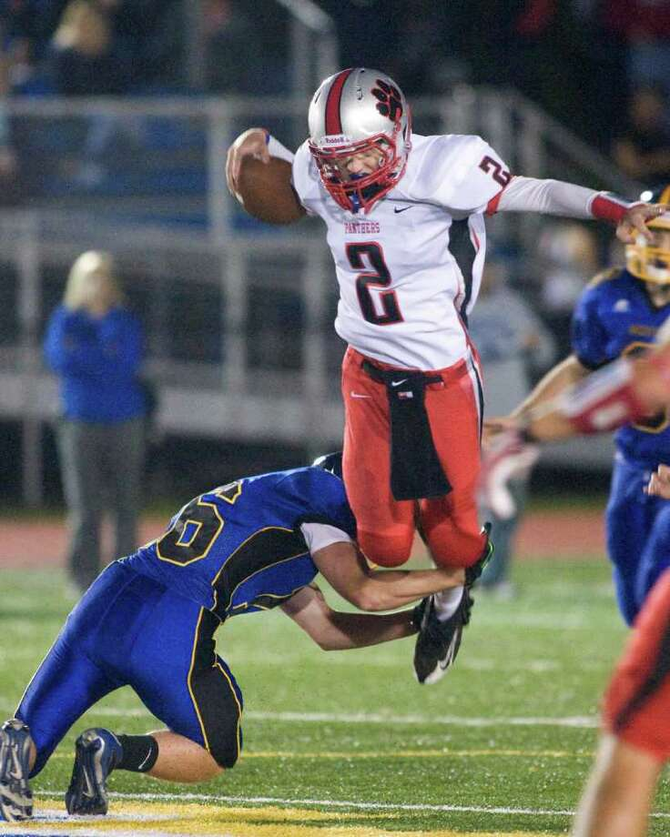 Pomperaug High School quarterback Eric Beatty goes airborne on a keeper play to pick up yardage before being stopped by Brookfield High School's Frank Colavito the SWC football game Friday, Sept. 16, 2011, at Brookfield High School. Photo: Barry Horn / The News-Times Freelance