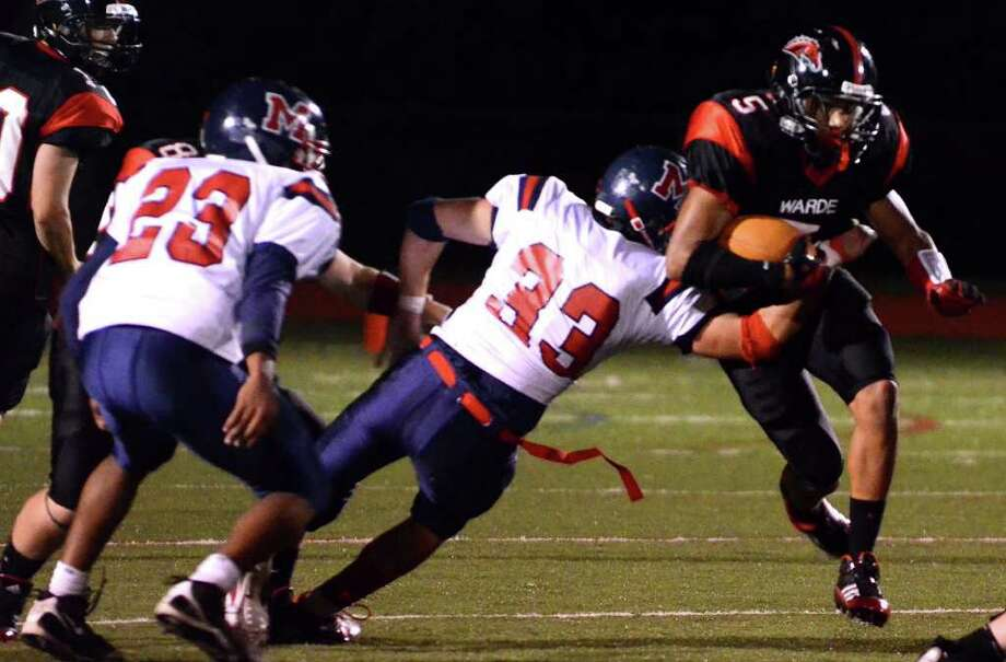 Brien McMahon's Zak O'Conner (33) snags Fairfield Warde's Devin Lofton (5) during the football game at Fairfield Warde High School on Friday, Sept. 16, 2011. Photo: Amy Mortensen / Connecticut Post Freelance