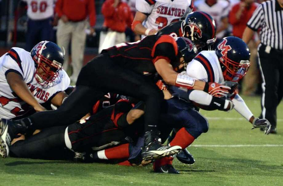 Fairfield Warde's Dario Pugliano (12) tackles Brien McMahon's Chris Jerome (34) during the football game against Brien McMahon at Fairfield Warde High School on Friday, Sept. 16, 2011. Photo: Amy Mortensen / Connecticut Post Freelance