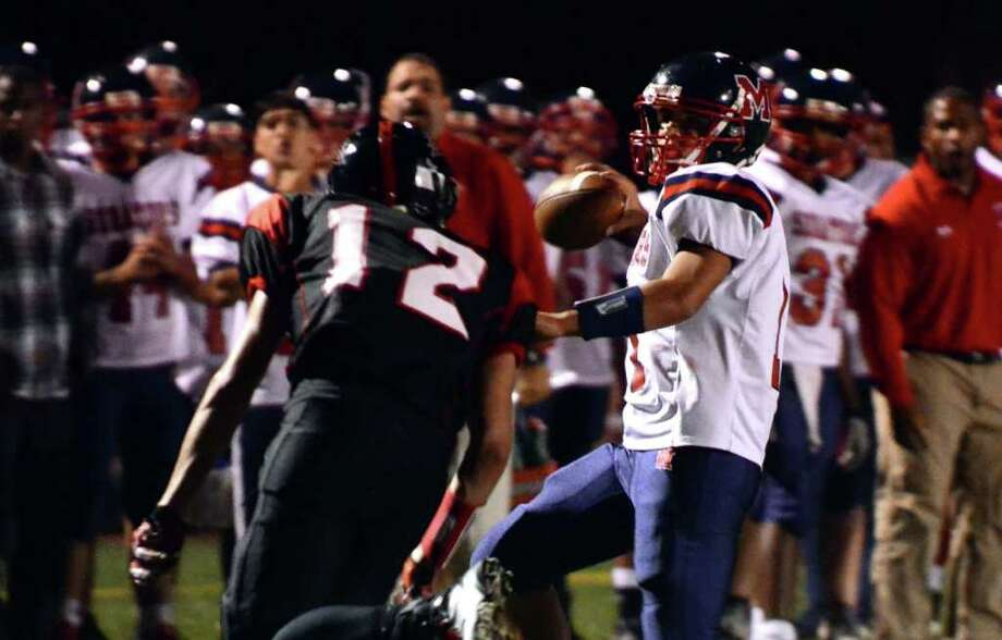 Brien McMahon's Damien Vega (11) looks to pass as Fairfield Warde's Dario Pugliano (12) defends during the football game at Fairfield Warde High School on Friday, Sept. 16, 2011. Photo: Amy Mortensen / Connecticut Post Freelance