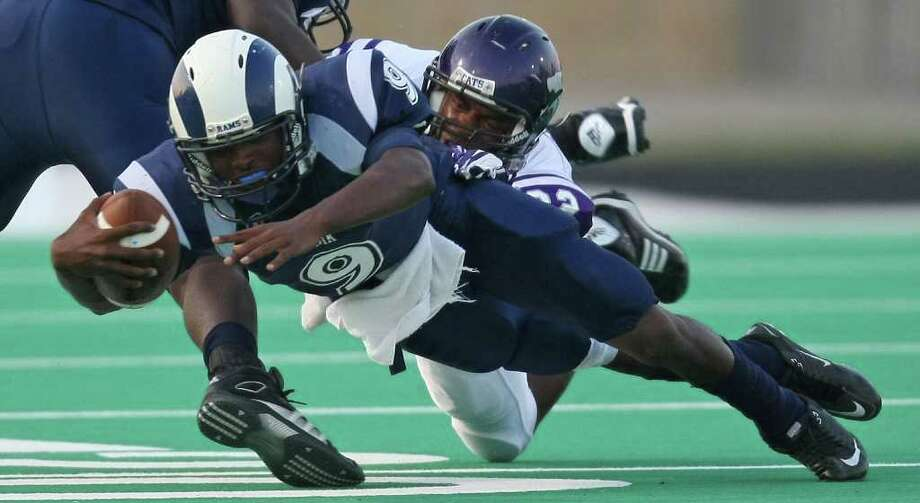 Elsik's Dominique Barnett dives for extra yardage past Angleton's Webster Jones during the first half of a high school football game, Friday at Crump Stadium. Photo: Eric Christian Smith, For The Chronicle