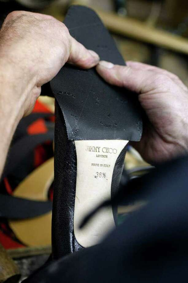A LITTLE PRESSURE: Croft glues a new sole on a shoe as he works in his Shoe Savers shop. Photo: Johnny Hanson / © 2011 Houston Chronicle