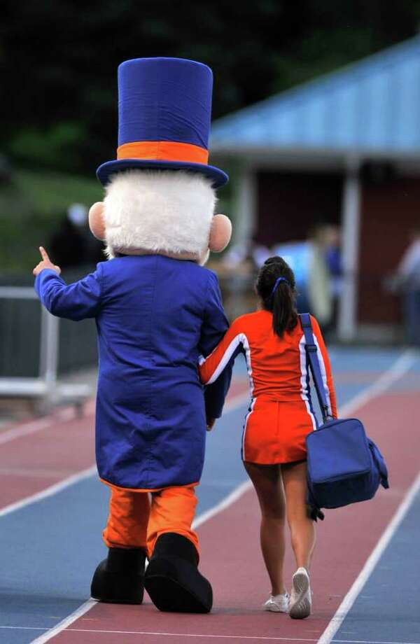 The Danbury Hatter mascot is led onto the field by a cheerleader before Danbury's game against Norwalk at Danbury High School on Friday, Sept. 16, 2011. Photo: Jason Rearick / The News-Times