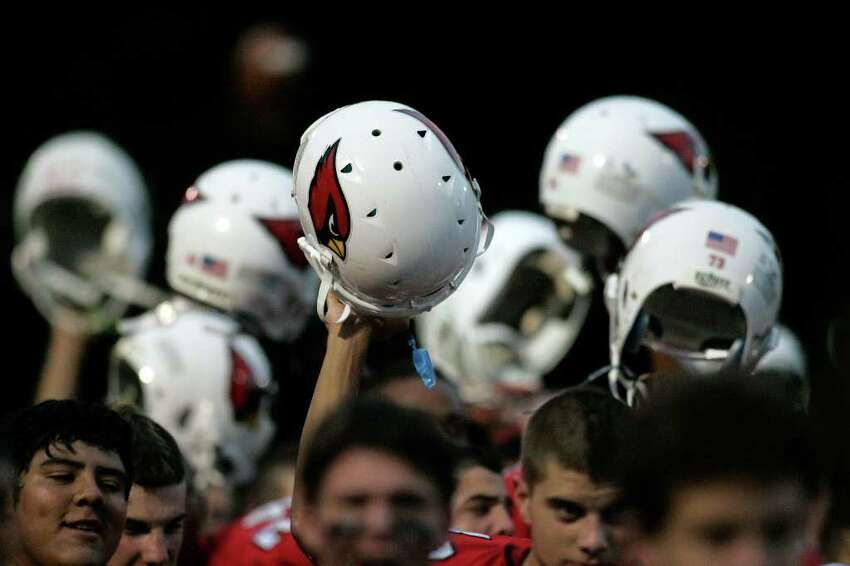 Members of the GHS football team raise them helmets in celebration prior to the start of the FCIAC battle between Greenwich and Ridgefield. © J. Gregory Raymond
