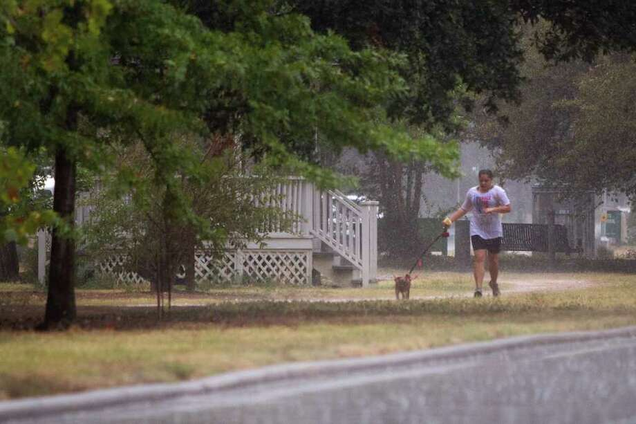 A runner gets caught in a brief shower while jogging along Heights Boulevard on Saturday. Photo: Smiley N. Pool, Houston Chronicle / © 2011  Houston Chronicle