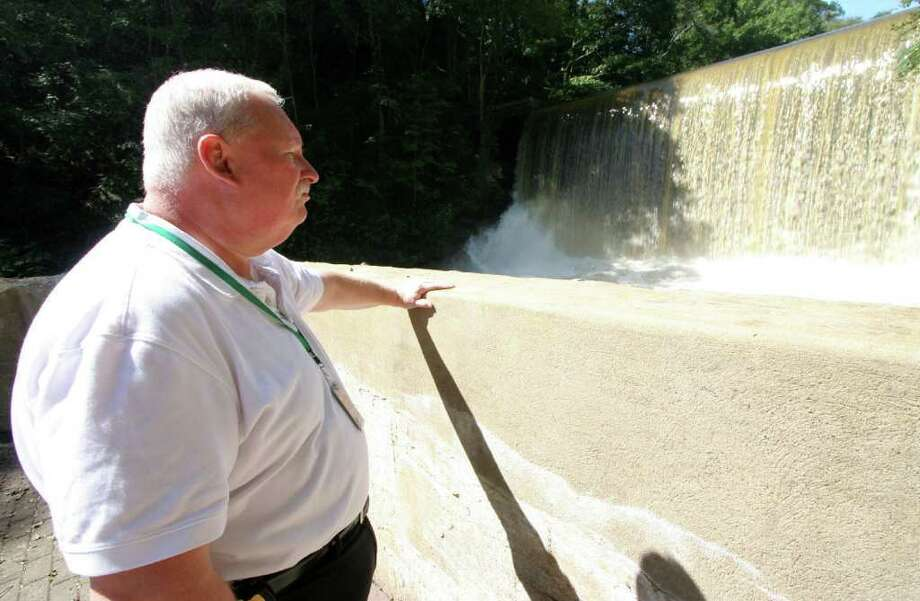 Greenwich Emergency Management Director Dan Warzoha inspects the Pemberwick Road dam Friday, Sept. 9, 2011. The Department of Energy & Environmental Protection sent a notice of violation to the dam's owners last week. Photo: David Ames / Greenwich Time