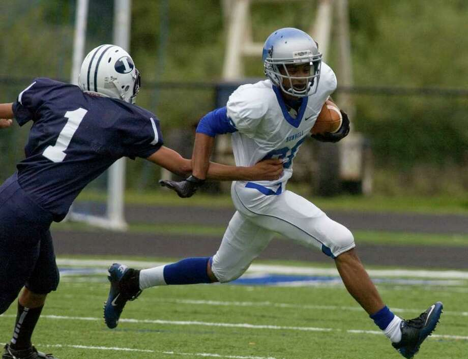 Bunnell's Devante Teel, right, runs past Immaculate's Darel Bowman during their game at Immaculate High School on Saturday, Sept. 17, 2011.  Bunnell won 46-21. Photo: Jason Rearick / The News-Times