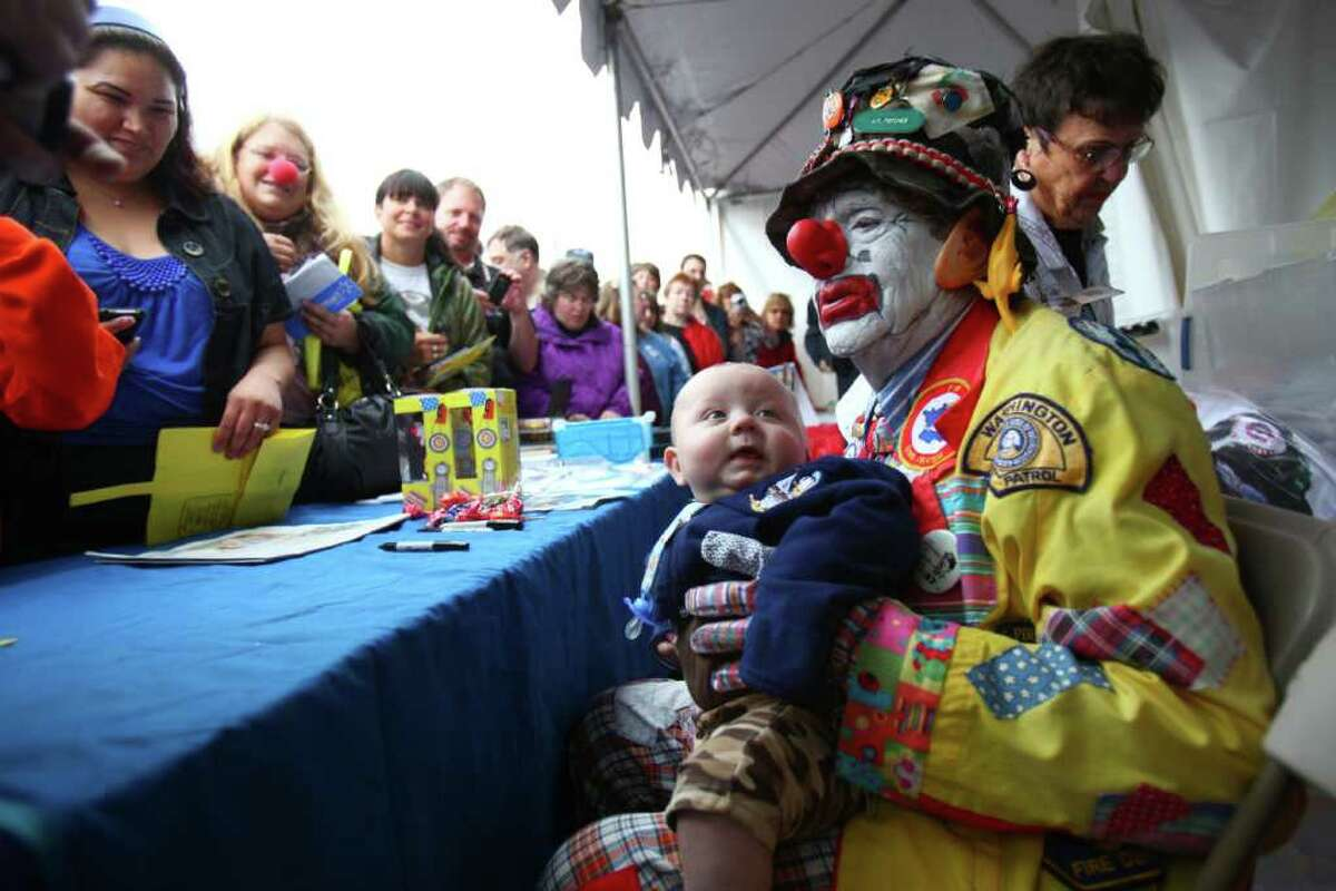 J.P. Patches holds onto Deano Dixon, 7 months, as crowds come to see the legendary clown during his final public performance on Saturday, Sept. 17, 2011 at the Fall Fishermen's Festival in Ballard. The man behind the legendary clown, Chris Wedes, is hanging up the costume after decades of entertaining kids in the Pacific Northwest.