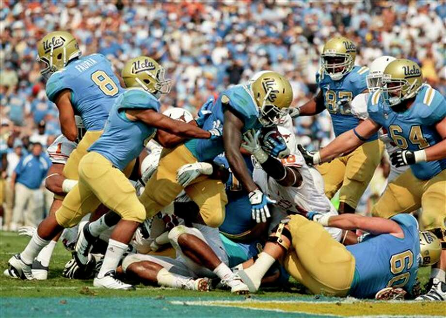 UCLA running back Derrick Coleman, middle, dives into the end zone for at touchdown during the second half of an NCAA college football game against Texas, Saturday, Sept. 17, 2011, at the Rose Bowl in Pasadena, Calif. Texas won 49-20. (AP Photo/Bret Hartman) Photo: BRET HARTMAN, Associated Press / FR139655 AP