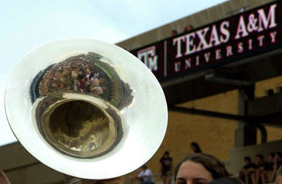 Part of the Texas A&M Fighting Aggie Marching band is reflected in a tuba before the game.