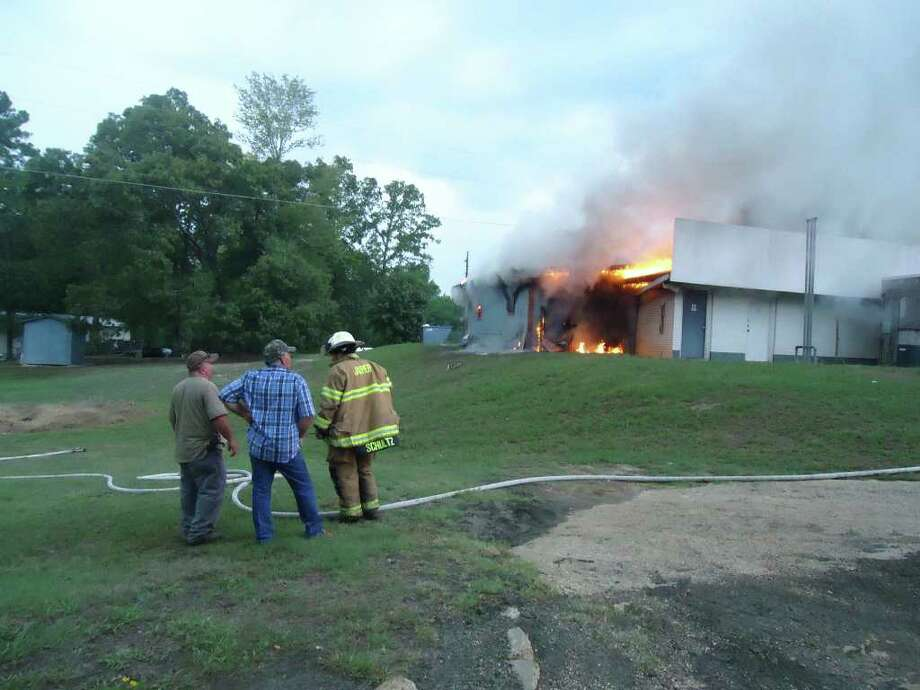 Owner Ronnie Miller, left, Sammy Dubose, center, and Jasper Fire's David Schultz discuss any dangers and the contents of the fire-stricken building and its layout. Photo: Jodie Warner