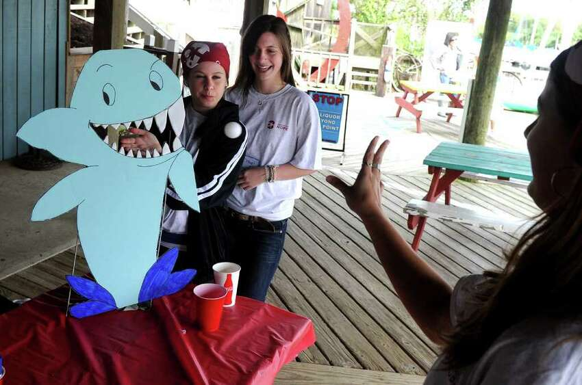 Volunteer Amy Rosten, right, tries to feed the shark as fellow volunteers Bronte More and Chloe Bartle, in center, look on as they take part in Pirate Fest, presented by Pirates for Prevention, which was held at Captain's Cove Seaport in Bridgeport, Conn. on Saturday September 17, 2011. Money raised from the event benifits P.A.W.S., a nonprofit shelter in Norwalk, and the ASPCA.