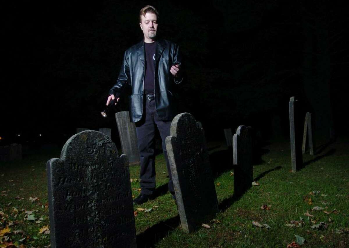 Nathan Schoonover, from Danbury, demonstraits how he investigates for ghosts at a grave yard in Danbury, Thursday, Oct. 8, 2009.